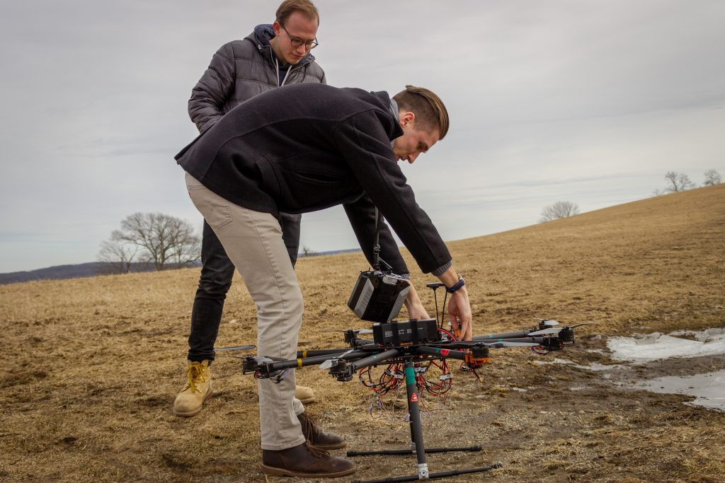 Ryan Heilemann '19 (foreground) and Josh Steil '19 check their drone before a recent flight test. (Christopher Larosa/UConn Photo)